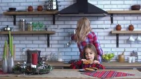 De jonge moeder in plaidoverhemd met het lange blonde haar koken ontbijt en kleine ongehoorzame meisjesbeet één koekje stock footage