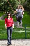 De jonge moeder slingert een kind in speelplaats Stock Afbeelding