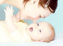 De jonge moeder speelt met haar weinig babymeisje Royalty-vrije Stock Fotografie