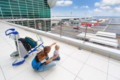 De jonge moeder toont aan de vliegtuigen van de babyjongen in luchthaven Royalty-vrije Stock Fotografie