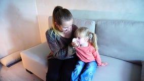De jonge moeder veegt neus aan dochter af, wordt het kind ziek stock footage
