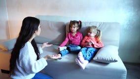 De jonge moeder vertelt twee dochters om zich in kleuterschool te verzamelen stock videobeelden