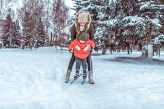 De jonge moeder verzekert de skis van de kinderen van het steunenkind, weinig jongenszoon 4 jaar De winter bospark, achtergrondsn stock foto