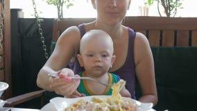 De jonge moeder voedt de baby op haar overlappingsdeegwaren in Italië Het jonge geitje 1 jaar, het is in een groene t-shirt stock video