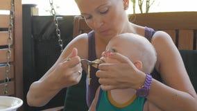 De jonge moeder voedt de baby op haar overlappingsdeegwaren in Italië Het jonge geitje 1 jaar, het is in een groene t-shirt stock videobeelden