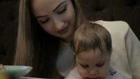 De jonge moeder voedt een klein meisje met een Suluguni-kaas stock videobeelden