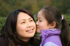 De jonge moeder wacht op kus van dochter Stock Foto's