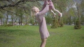 De jonge moeder werpt op haar omhoog weinig dochter en vangsten, beide lach Gelukkige onbezorgde kinderjaren In openlucht het rus stock videobeelden