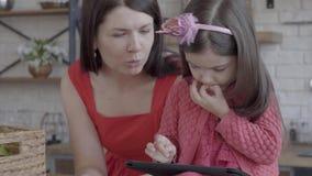 De jonge moeder zette op het lijstvakje met brood en het spreken aan haar kleine dochter die spelen op de tablet speelt stock video