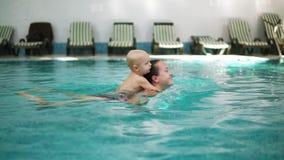 De jonge moeder zwemt in de pool die haar tegenhouden weinig leuke peuter op haar Aanbiddelijk omhelst weinig jongen van hem stock footage