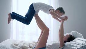 De jonge moederspelen met haar zoon op bed, dwaas rond en hebben samen pret in langzame motie stock video