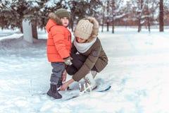 De jonge moedervrouw maakt de skis van kinderen, weinig jongenszoon 3 recht jaar De winter bospark, achtergrondsneeuwafwijkingen royalty-vrije stock foto's