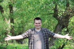 De jonge mollige man spreidde wijd apart de radiaal ogen uit Glimlacht ruim In het park onder het heldergroene gebladerte royalty-vrije stock foto