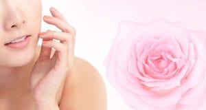De jonge mond van de vrouwenglimlach met roze roze bloem Royalty-vrije Stock Foto