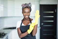 De jonge mooie Afrikaanse rubberhandschoenen die van de vrouwenslijtage voor het schoonmaken bij homw voorbereidingen treffen stock foto's