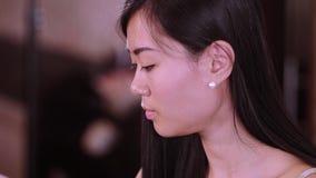 De jonge mooie Aziatische vrouw eet Sushi in een restaurant stock video