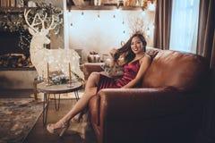 De jonge mooie Aziatische vrouw is sexy rode kledingszitting thuis dichtbij Kerstmisboom in comfortabel binnenland Binnenland met royalty-vrije stock foto's