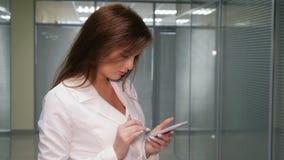 De jonge mooie bedrijfsvrouw schrijft SMS aan uw mobiele telefoon stock footage