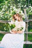 De jonge mooie bloemen van de meisjesholding in hun handen royalty-vrije stock foto's