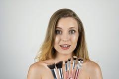 De jonge mooie blonde vrouw die roze borstels houden kijkt verbaasde geïsoleerde witte achtergrond royalty-vrije stock afbeeldingen