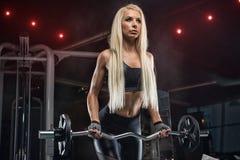 De jonge mooie bodybuilder van de meisjesatleet bij de gymnastiek die exerci doen stock fotografie