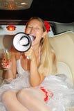 De jonge bruid zit in auto, schreeuwt in megafoon. stock foto