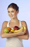 De jonge mooie brunette houdt fruit Royalty-vrije Stock Afbeeldingen