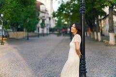 De jonge mooie donker-haired vrouw, bevindt zich met haar terug tegen phonor in de straat in het stadscentrum op een zonnige dag, Stock Fotografie