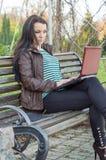 De jonge mooie donkerbruine student in profiel zit Royalty-vrije Stock Fotografie