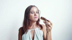 De jonge mooie donkerbruine vrouw eet een heerlijke cake op een witte achtergrond Langzame Motie 3840x2160 stock footage