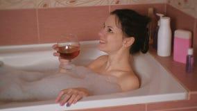 De jonge mooie donkerbruine vrouw neemt een bad, drinkt whisky en het glimlachen stock footage