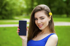 De jonge mooie donkerbruine vrouw toont een nieuwe slimme telefoon Royalty-vrije Stock Foto's