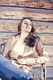 De jonge mooie donkerbruine vrouw zit als wapenvoorzitter Stock Fotografie