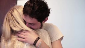 De jonge mooie donkere haired man koestert langharige blondevrouw bij deuropening stock videobeelden
