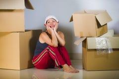 De jonge mooie en gelukkige Aziatische Koreaanse vrouw wekte thuis de uitpakkende bezittingen van de woonkamervloer van kartondoz stock foto