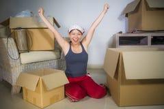 De jonge mooie en gelukkige Aziatische Koreaanse vrouw wekte thuis de uitpakkende bezittingen van de woonkamervloer van kartondoz stock foto's