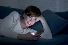 De jonge mooie en gelukkige rode haarvrouw op haar jaren '20 of jaren '30 die op huis liggen gaat liggen of bed gebruikend mobiel stock foto's