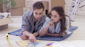 De jonge mooie familie bespreekt reparaties in hun nieuwe woning stock videobeelden