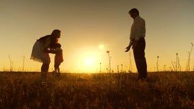 De jonge mooie familie op gebied met kind bij zonsondergang, een klein kind leert om met mamma en papa, Langzame motie te lopen stock video
