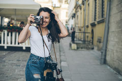 De jonge mooie gang van de vrouwenfotograaf door oude stadsstraat met retro camera royalty-vrije stock afbeeldingen