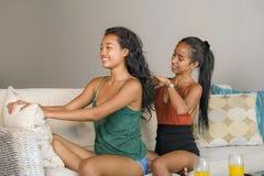 De jonge mooie gelukkige Aziatische meisjes gaan liggen thuis met één meisje die het haar van de andere vrouw borstelen die het v royalty-vrije stock afbeeldingen
