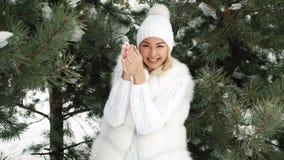 De jonge mooie het glimlachen sneeuw van de blondeontploffing met haar handen stock footage
