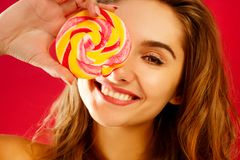 De jonge mooie de holdingslolly van de smileyvrouw overhandigt binnen rode bac royalty-vrije stock foto