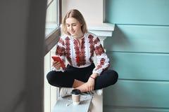 De jonge mooie Kaukasische studente die een vyshyvanka dragen, een traditioneel Oekraïens geborduurd overhemd controleert haar stock afbeelding