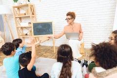 De jonge mooie leraar met bril geeft boek aan studentenzitting op vloer stock foto