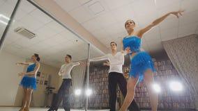 De jonge mooie man en vrouw die en Latijnse dans in kostuums in de Studio de repeteren, sluiten omhoog, in actie dansen stock afbeeldingen