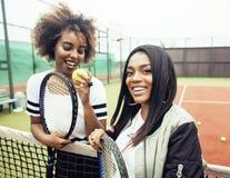 De jonge mooie meisjes die op tennisbaan hangen, vormen gekleed modieus swag, het beste vrienden gelukkige samen glimlachen Stock Foto's
