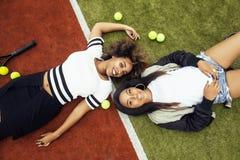 De jonge mooie meisjes die op tennisbaan hangen, vormen gekleed modieus swag, het beste vrienden gelukkige samen glimlachen Royalty-vrije Stock Afbeeldingen