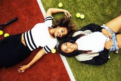 De jonge mooie meisjes die op tennisbaan hangen, vormen gekleed modieus swag, het beste vrienden gelukkige samen glimlachen Stock Fotografie