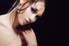 De jonge mooie meisjes heldere make-up met een natte blik glanst, donkere achtergrond Stock Afbeelding